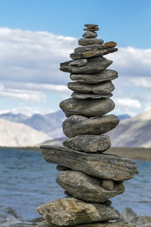large and diverse stack of stones balancing on a lake background