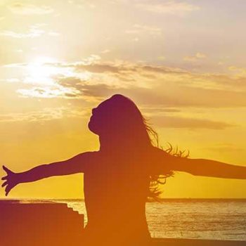 silhouette of woman at sunset on the beach with her arms wide and her head looking to the sky in joy