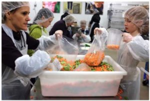 children and parents assist in packing fresh vegetables at Oregon Foodbank