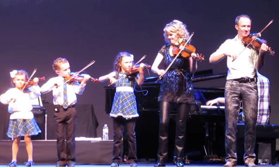 Natalie MacMaster with husband and three children playing fiddles in the Cape Breton style.