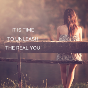 Picture of young woman sitting on bench looking out at a lake. Quote is: Unleash The Real You