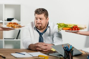 making a lunch choice that's healthy. Man is choosing between pizza and celery and carrots