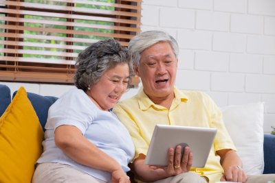 senior couple looking at tablet while doing facetime with family