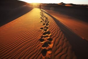 footprints in the sand, one step at a time with person toward the top of the hill