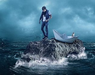 young man stranded on rock outcropping with a paper boat and a cat in a stormy sea