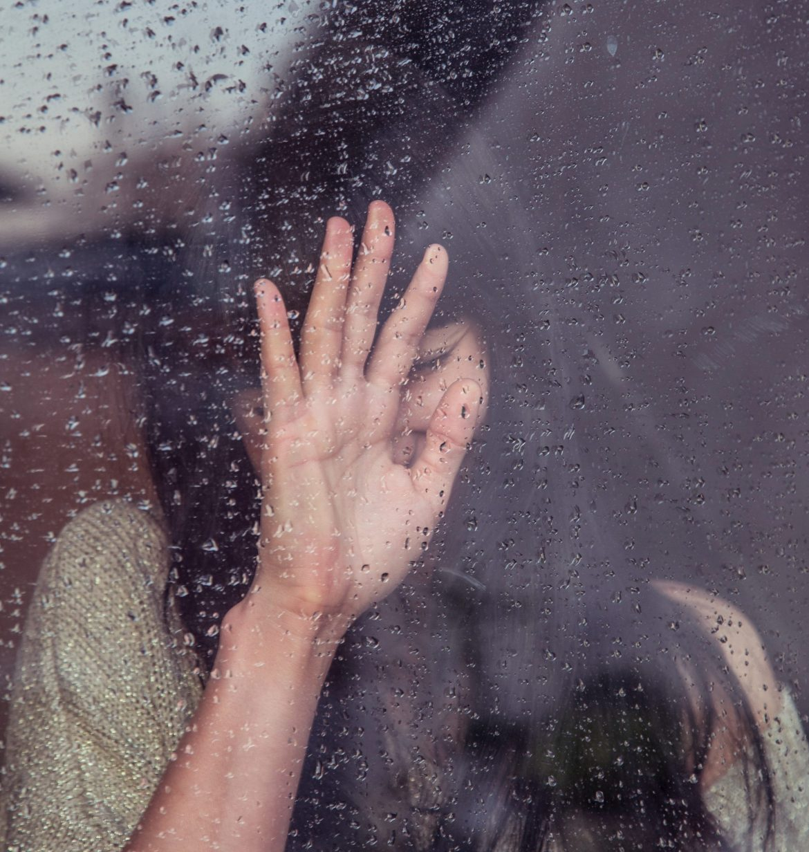 woman pressed against glass window with rain outside