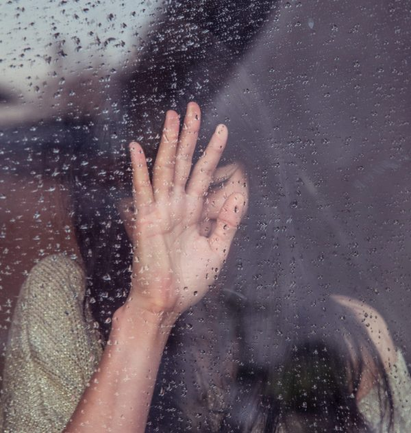 woman pressed against glass window with rain outside looking sad