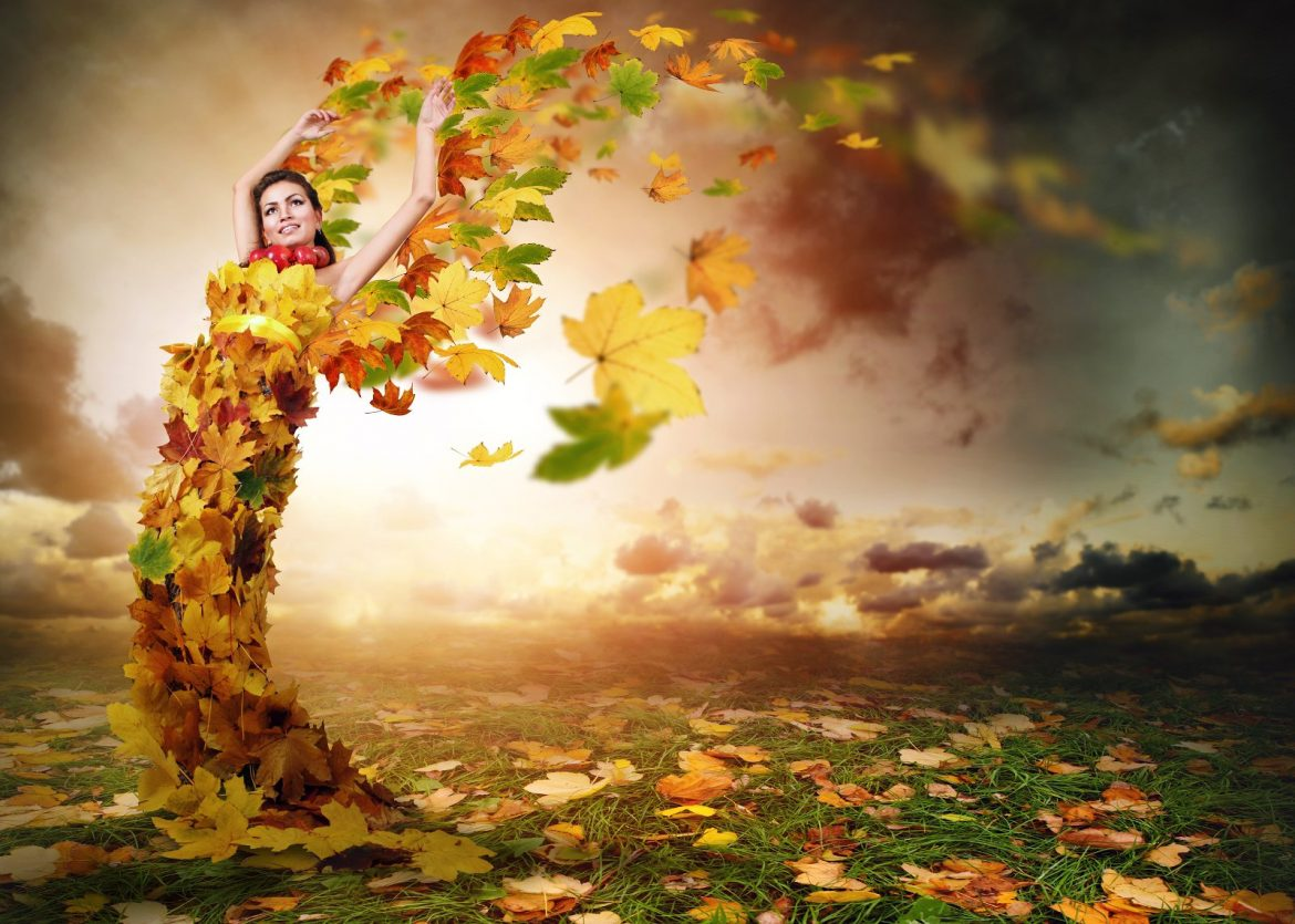 woman adorned in autumn leaves reaching for the sky with storm clouds in the background